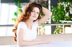 Una mujer joven que se sienta en un café Imagen de archivo