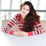 Una mujer joven que se sienta en un café Fotografía de archivo