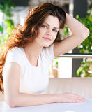 Una mujer joven que se sienta en un café Foto de archivo libre de regalías