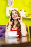Una mujer joven que se sienta en un café con el teléfono celular Imágenes de archivo libres de regalías
