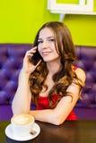 Una mujer joven que se sienta en un café con el teléfono celular Fotos de archivo libres de regalías