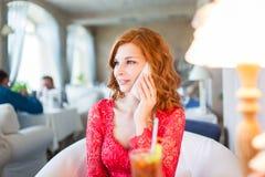 Una mujer joven que se sienta en un café con el teléfono celular Fotografía de archivo libre de regalías