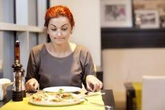 Una mujer joven que se sienta en un restaurante, smilin Fotografía de archivo