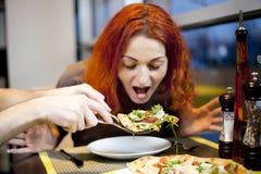 Una mujer joven que se sienta en un restaurante, smilin Fotos de archivo