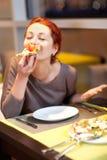 Una mujer joven que se sienta en un restaurante, smilin Imagenes de archivo