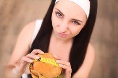 Una mujer joven que sostiene una hamburguesa en una cinta métrica Una muchacha se coloca en un fondo de madera La visión desde la Foto de archivo libre de regalías