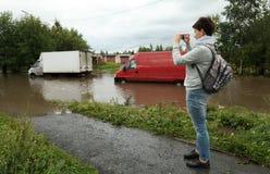 Una mujer joven que toma las fotos de coches con los motores atascados en agua Imagen de archivo