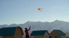 Una mujer joven que vuela su cometa en un campo con las montañas y los glaciares almacen de video