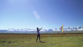 Una mujer joven que vuela su cometa en un campo con las montañas y los glaciares almacen de metraje de vídeo