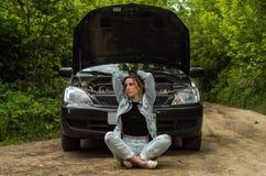 Una mujer joven rompió un coche en el camino y ella se sienta delante de un coche con una capilla abierta en la confusión y para  Fotos de archivo