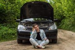 Una mujer joven rompió un coche en el camino y ella se sienta delante de un coche con una capilla abierta en la confusión y para  Foto de archivo