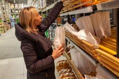 Una mujer joven rubia en una chaqueta larga elige compras del rato de la comida foto de archivo