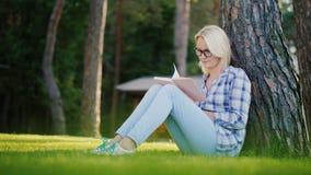 Una mujer joven rubia en vidrios lee un libro en el parque Se sienta cerca de un árbol, luz hermosa antes de la puesta del sol, v metrajes