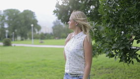 Una mujer joven rubia que disfruta del tiempo ventoso en un parque metrajes