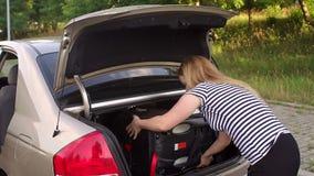 Una mujer joven saca un asiento de carro del bebé del tronco de un coche almacen de metraje de vídeo