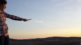 Una mujer joven señala al rastro que permanece en el cielo del avión almacen de video