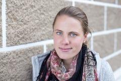 Una mujer joven se coloca delante de una pared de ladrillo mientras que sonríe en la cámara Foto de archivo libre de regalías