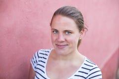 Una mujer joven se coloca delante de una pared rosada mientras que Imagen de archivo libre de regalías