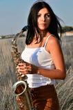Una mujer joven se coloca en el campo y sostiene un saxofón fotos de archivo
