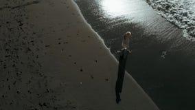 Una mujer joven se coloca en una playa negra en un vestido elegante largo en Los Gigantes, Tenerife, islas Canarias, España almacen de video
