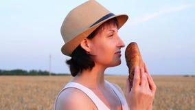 Una mujer joven se coloca en un campo de trigo y sostiene el pan, trayendo a su cara e inhalando el aroma Agricultura almacen de metraje de vídeo
