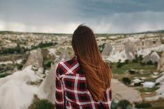 Una mujer joven se coloca en un punto álgido y mira la vista de las colinas de Cappadocia en tiempo lluvioso Visión hermosa Foto de archivo libre de regalías