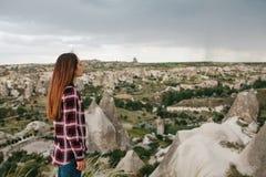 Una mujer joven se coloca en un punto álgido y mira la vista de las colinas de Cappadocia en tiempo lluvioso Visión hermosa Fotos de archivo libres de regalías
