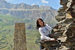 Una mujer joven se coloca sonriente cerca de una pared arruinada contra una torre imagen de archivo libre de regalías