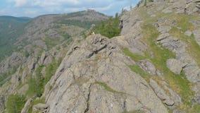 Una mujer joven se está sentando al borde de un acantilado impresionante de la montaña, tiro aéreo de la órbita almacen de video