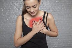 Una mujer joven se está sosteniendo el pecho, ataque del corazón o más allá del horizonte posible imagen de archivo