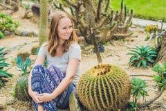 Una mujer joven se sienta en la tierra entre el cactus Concepto espinoso foto de archivo