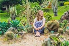 Una mujer joven se sienta en la tierra entre el cactus Concepto espinoso imágenes de archivo libres de regalías