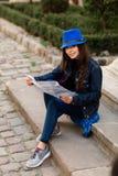 Una mujer joven se sienta en las escaleras en el patio viejo, y lee el mapa Lviv, Ucrania fotografía de archivo libre de regalías