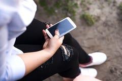 Una mujer joven se sienta en un banco de parque para escuchar sus tonos preferidos Imagen de archivo libre de regalías