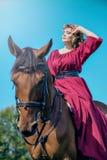 Una mujer joven se sienta en un vestido rojo se está sentando en la parte de atrás de un caballo marrón imagenes de archivo