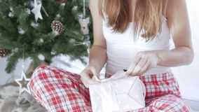 Una mujer joven se sienta por el árbol de navidad y embala un regalo almacen de metraje de vídeo