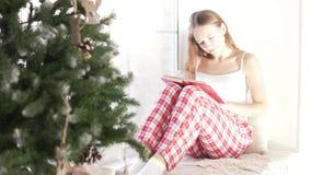 Una mujer joven se sienta por la mañana en el árbol de navidad almacen de metraje de vídeo