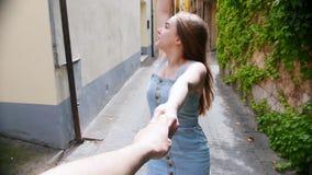 Una mujer joven sigue a su novio por una mano a través de una calle en Italia y la mirada alrededor metrajes