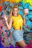 Una mujer joven sonriente con un cubo de pintura Fotografía de archivo