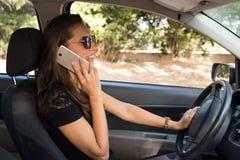 Una mujer joven sonriente en el coche habla en el teléfono elegante y conduce Fotos de archivo libres de regalías