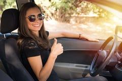 Una mujer joven sonriente se sienta en el coche con los pulgares para arriba Foto de archivo libre de regalías