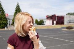 Una mujer joven sostiene un perrito caliente mordido imágenes de archivo libres de regalías