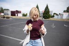 Una mujer joven sostiene un perrito caliente mordido fotografía de archivo libre de regalías