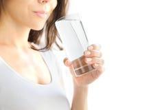 Una mujer joven sostiene un vidrio de agua en su mano y está a punto de beberla Fondo blanco Copie el espacio foto de archivo libre de regalías