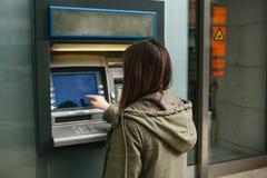 Una mujer joven toma el dinero de una atmósfera Ase una tarjeta de la atmósfera Finanzas, tarjeta de crédito, retiro del dinero imagen de archivo