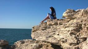 Una mujer joven toma el sol en una roca almacen de metraje de vídeo