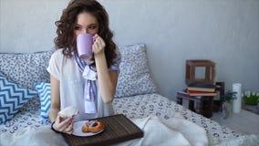 Una mujer joven toma una mordedura de una torta y bebe el café con leche en cama almacen de metraje de vídeo