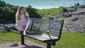 Una mujer joven utiliza un smartphone y bebe el café en banco en parque almacen de video