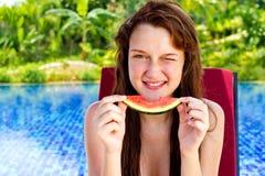 Una mujer joven y atractiva que come la sandía cerca Foto de archivo