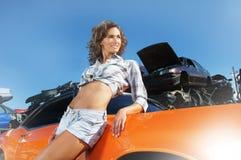 Una mujer joven y atractiva que presenta cerca de un coche imagen de archivo libre de regalías
